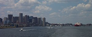 An LNG carrier passes just offshore of downtown Boston, under Coast Guard and police escort.