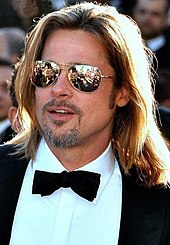 A Caucasian male in his late-40s wears aviators sunglasses, has long blonde hair and a short grey beard. He wears a black suit and white shirt with a black bow-tie.