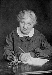 A grandmotherly woman of about 70 is seated, pen in hand, at a desk with a writing pad.
