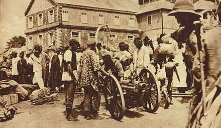 "British West African Campaign troops in Freetown, 1914-1916. Published caption: ""British expeditionary force preparing to embark at Freetown to attack the German Cameroons, the main object of the attack being the port of Duala. Auxiliary native troops were freely used in African warfare."" British Expeditionary Force in Freetown, 1919.jpg"