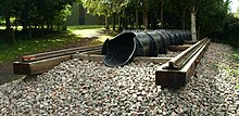 Exterior in woodland. a short section of railway line on wooden sleepers with a cast iron pipe of approximately one foot diameter, running inline with the rails