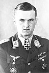 The head and shoulders of a young man, shown in semi-profile. He wears a military uniform with an Iron Cross displayed at the front of his shirt collar. His hair isshort and combed to his right, his nose is short, and his facial expression is determined; looking into the camera.