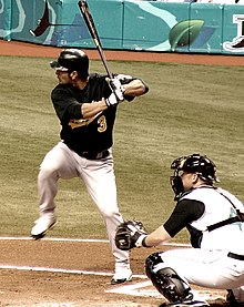 A man in a dark baseball jersey, batting helmet, and white pants takes a left-handed baseball swing while another man kneels wearing catcher's gear behind him.