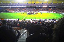 A team celebrates in the center of a soccer field while fans in stand on both sides cheer.