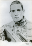 Hand-drawn pencil portrait of a soldier holding an assault rifle. He has cropped hair and is facing the viewer.