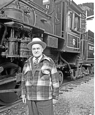 """Newhalem, Washington - Dana Currier, one of the key figures in the creation of Newhalem, poses in 1954 with the 2-6-2 locomotive built for Seattle City Light by Baldwin Locomotive Works in 1928 and known as """"Old Number Six"""""""