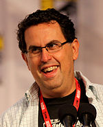 A man with black hair and glasses speaks into a microphone.