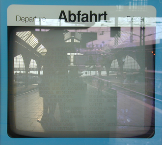 Glossy display - Railway timetable shown on a CRT display with reflective vandal-proof cover glass, exhibiting distinct reflections from ambient light sources (sky, lamps).  The visual information can only be read (with very low contrast) in the regions with shadow.
