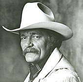 A man with a large mustache wearing a cowboy hat and light-coloured jacket