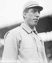 A man in a light-colored baseball uniform and baseball cap looks to the right of the image. He has a long face with a strong nose and chin, along with short hair seen under the band of his cap.