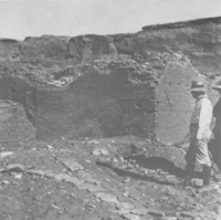 A black-and-white photo of a man standing next to a large ruin