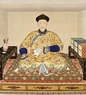 painted portrait of a man with small eyes and a thin mustache sitting cross-legged on what appears to be a large embroidered cushion placed on a low platform. He is holding a folded string-bound book in his left hand, and flanked on each side by a low table on which are posed boxes of books (to his left) and a cup containing brushes (on his right). He is wearing an opulent yellow imperial robe with five-clawed dragons, clouds, and water patterns.