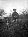 En pojke med en hund sitter på en sten - Nordiska Museet - NMA.0057550.jpg