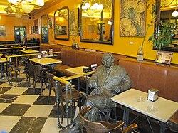 Estatua dedicada a Torrente Ballester, en el Café literario Novelty, fundado en 1905, en la Plaza Mayor de Salamanca, obra del escultor Fernando Mayoral. Se considera que fue el botánico alemán Léonard Rauwolf quien, por primera vez, describió el café en un libro publicado en 1583.