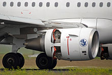 A turbofan engine is shown on an aircraft decelerating on a runway. Small doors on the rear half engine are open.
