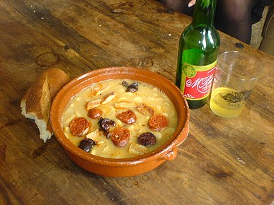 Fabada asturiana, a rich Spanish bean stew, as typically served with crusty bread and Asturian cider