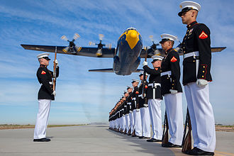 United States Marine Corps Silent Drill Platoon - A U.S. Marine Corps C-130T Hercules aircraft with the Blue Angels, the Navy's flight demonstration squadron, flies over Marines with the Silent Drill Platoon at Marine Corps Air Station Yuma, Arizona.