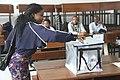 Femme votant à Kinshasa devant des scrutateurs.jpg
