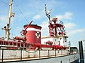 Photograph of the fireboat Duwamish at dock as a museum ship. The picture clearly shows several items of firefighting equipment, including water cannons, ladders, floodlights, pipelines, hose fittings, and the Seattle Fire Department seal on the funnel.