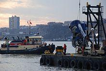 Photo de la récupération du moteur. À gauche, un navire supervise les opérations tandis qu'à droite, sur la berge, une grue tire le moteur endommagé du fleuve.