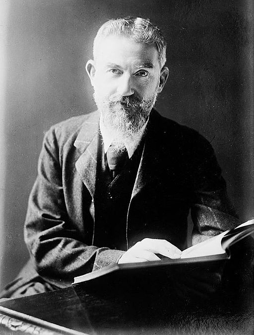 George Bernard Shaw at desk with book