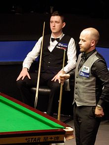 Wilson is sat with Brecel about to play a shot