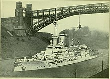 A large warship passing through a narrow canal, with a large railway arch bridge above it