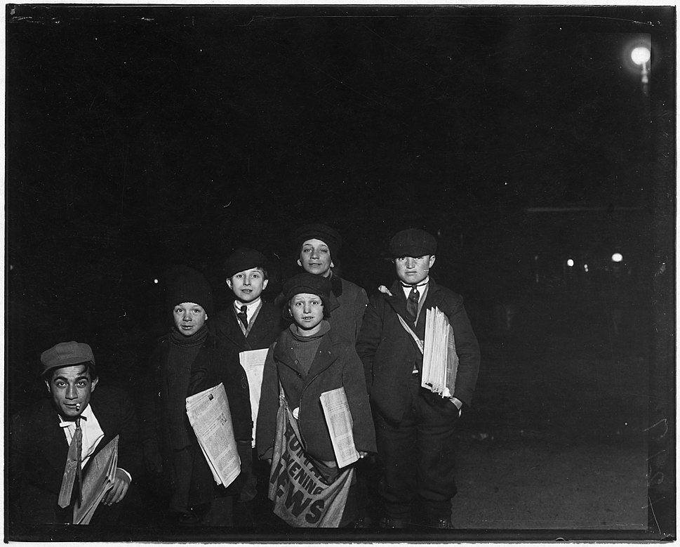 "Group on Court St. selling around the ""Shea Theatre,"" 8 P.M. Boy in center, Vito Bucheto, 10 years old. Behind him to... - NARA - 523275"