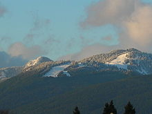 Grouse mountain's snow terrain, as seen from Burnaby, featuring the Cut (left) and expert peak runs (right).