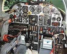 Aircraft cockpit with numerous old circular dials and gauges. In front of the controls is a black stick control column.