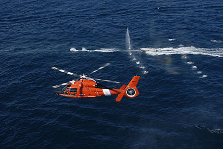 A United States Coast Guard helicopter firing warning shots at a non-compliant boat during training. HITRON MH-65C Fires warning shots.jpg