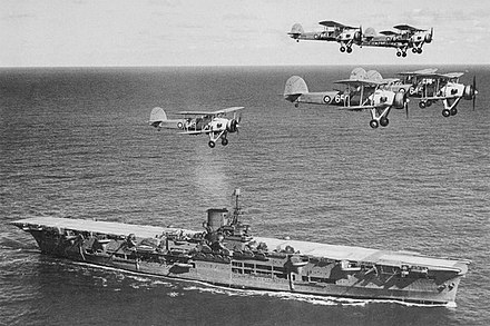 The Royal Navy's HMS Ark Royal in 1939, with Swordfish biplane bombers passing overhead. The British aircraft carrier was involved in the crippling of the German battleship Bismarck in May 1941 HMS Ark Royal h85716.jpg