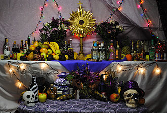 Haitian Vodou - Vodou altar during a celebration for Papa Guédé in Boston. This altar has offerings to three nations (nanchons) of loa: at top right are offerings to Rada spirits; at top left are those for the Petwo family; and those at bottom are for Guédé.