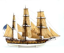 A scale model of a three-masted sailing rigged with square sails seen from the side at a right angle. It has 14 cannons protruding from gunports below the weather deck. Between the gunports are multiple smaller ports designed for oars. The hull is a light brown color, painted white below the waterline.