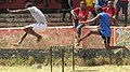 High school students compete in a 200M steeplechase during their regional games.jpg