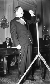 Long raises his fist as he speaks into a microphone