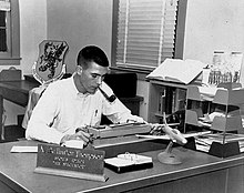 Photograph of a man with a crew cut at work writing, sitting at a desk that has a model fighter plane on it
