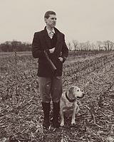 A hunter poses with a Lab in a snowy corn field.