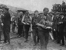 A team of 6 or seven men, covered in coal dust and each carrying their respirator packs. They are watched by a crowd of onlookers.