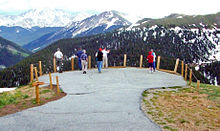 A small paved area encircled by a guardrail with wooden posts and ropes. People are standing in it looking at high snow-capped mountains in the distance