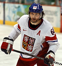 An ice hockey player holds his stick across his body. He is wearing a blue helmet and a blue and white uniform.