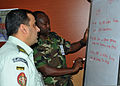 Jordanian Armed Forces Maj. Ali Almashaqbeh, left, and Lt. Col. Joseph Karegire of Rwanda discuss military and civilian coordination in a typical U.N. mission during exercise Shanti Doot-3 March 18, 2012, at 120318-Z-KC839-062.jpg