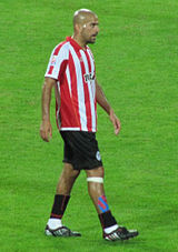 A photograph of a bald man wearing a red and white striped shirt, black shorts and black socks.
