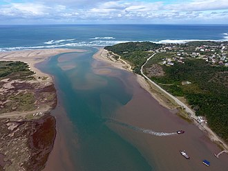 Great Kei River - Aerial photograph of the mouth of the Great Kei River as it meets the Indian Ocean.  The river ferry allowing vehicles and passengers to cross the river can be seen in the foreground.