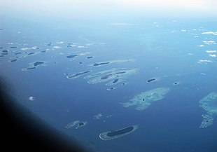 The archipelago of Kepulauan Seribu focusing on the connected islands of Pulau Kelapa and Pulau Harapan in the centre of the picture.