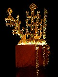 A shiny gold crown resembling trees, exhibited in a very dark room. It has beads of rock crystal and translucent and curved green jade ornaments
