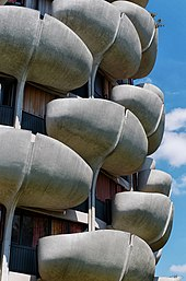 The curved balconies in front of each apartment's windows