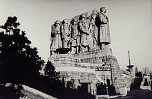 Un monument de grande hauteur représentant Staline à la tête d'une file d'individu.