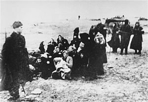 The Holocaust in Latvia - Members of a Latvian self-defence unit assemble a group of Jewish women for execution on a beach near Liepāja, 15 December 1941.