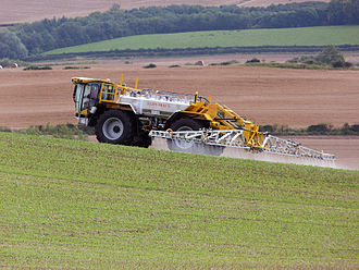 Pesticide - A Lite-Trac four-wheeled self-propelled crop sprayer spraying pesticide on a field